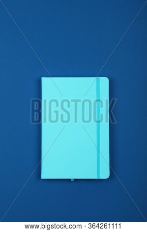 One Closed Blue Faux Leather Cover Notebook On Vivid Blue Paper Background, Flat Lay, Directly Above