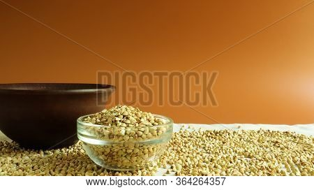 Green Buckwheat In A Glass Transparent Bowl On A Brown Background. Healthy Groats. Organic Raw Non-f