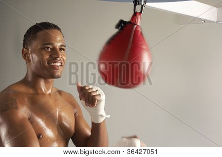 Young African American athlete working out on a speed bag in a gym