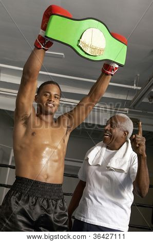 African American boxer holding championship belt with coach
