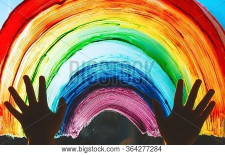 Close-up Photo Of Child's Hands Touch Painting Rainbow On Window. Family Life Background. Image Of K