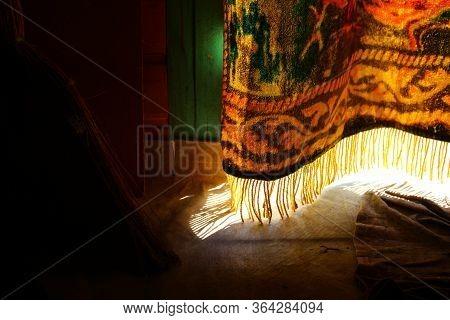 Sunlight Penetrates Through Cracks In The Curtain On The Doorway