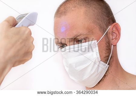 Body Temperature Measurement. A Male Person With Protective Face Mask Being Measured Body Temperatur
