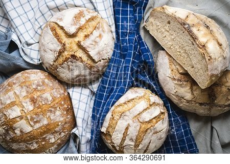 Several Loaves Of Bread On Kitchen Towels, Above View. Home-baked Sourdough Bread. Crusty Bread Top