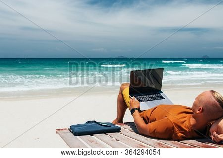 Young Guy With Long Hair By The Sea On A Sunny Day, Working Using His Laptop, Working Remotely With