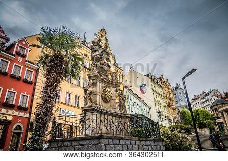 Karlovy Vary, Czech Republic, May 9, 2019: Holy Trinity Column Near Market Colonnade Trzni Kolonada