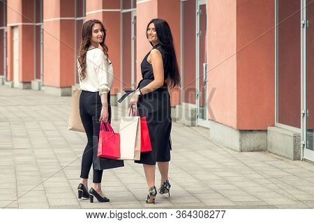 Back Side View Of Two Girls Are Walking Together, Carrying Colorful Paperbags Near Shopping Center A