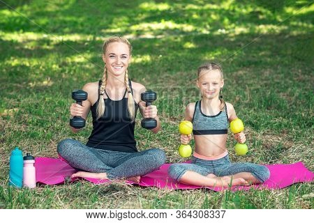 Mother With Daughter Are Training With Dumbbells On The Roll Mat At The Park, Woman And Child Is Tra