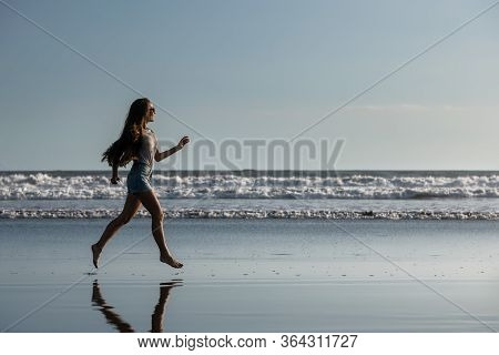 Happy Beautiful Girl Runs Alone At Ocean Beach