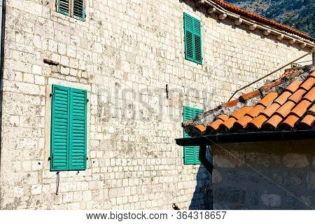 Authentic House With A Stone Wall, With Beautiful Old Open Windows And With Green Shutters, And With