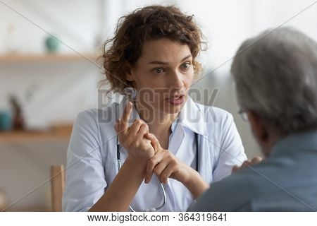 Female Physician Talking To Senior Patient At Visit In Hospital