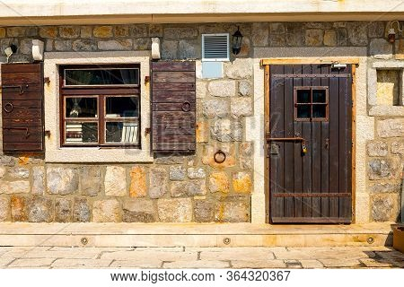 Authentic House With A Stone Wall, With A Beautiful Old Window And Brown Shutters, Background.