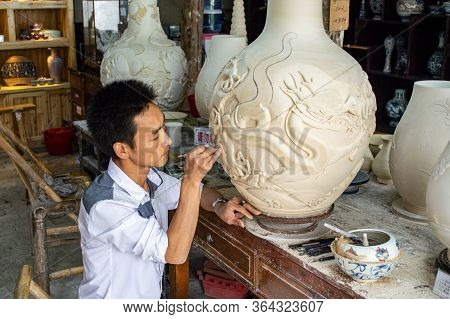 Jingdezhen, Jiangxi Province / China - May 29, 2014: Porcelain Craftsman Working In The Pottery Work