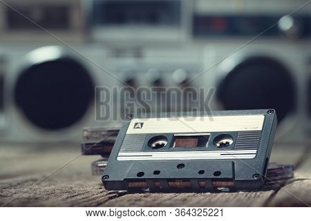Compact Cassette Tape On The Foreground With A Cassette Recorder On The Background