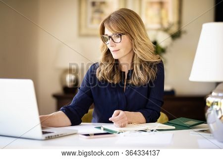 Middle Aged Woman Sitting Behind Her Laptop While Working At Home