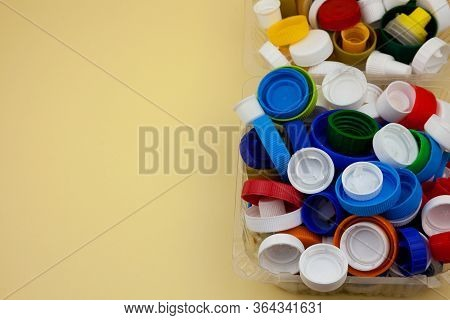 Sort Plastic Bottle Caps. Recycling. Zero Waste. Yellow Background With Place For Text. Eco Friendly