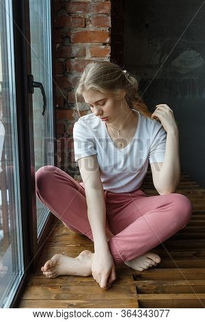 Stay Home Concept: Spending Time In Boredom. Young Pretty Girl Sitting On Window Sill In Cozy Loft R