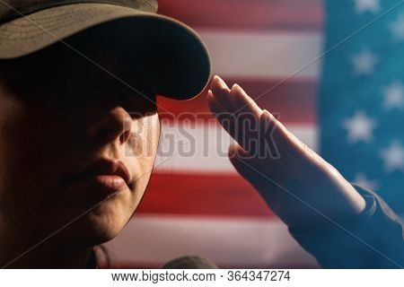 Memorial Day. A Female Soldier In Uniform Salutes Against The Background Of The American Flag. Close