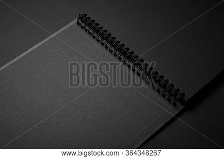 Blank Black Notebook On A Black Table, Mockup Photo. Blank Black Cover Template With Copy Space For