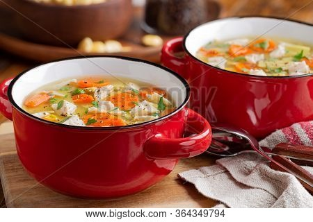 Closeup Of Two Bowls Of Chicken Noodle And Vegetable Soup Soup On A Wooden Table