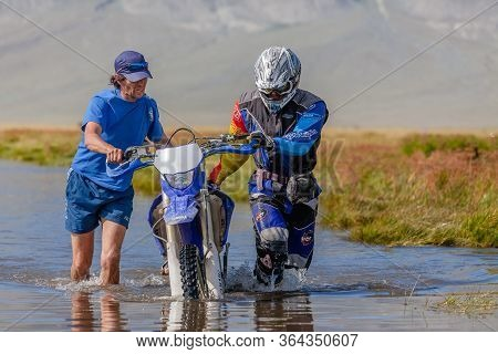 Altai, Mongolia - June 14, 2017: Two Men Are Pushing A Motorcycle Along A Road Flooded With Water. A