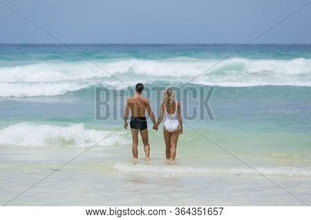 Lover Couple Enjoy Their Vacation At Tropical Beach Together In The Blue Water Of The Indian Ocean,