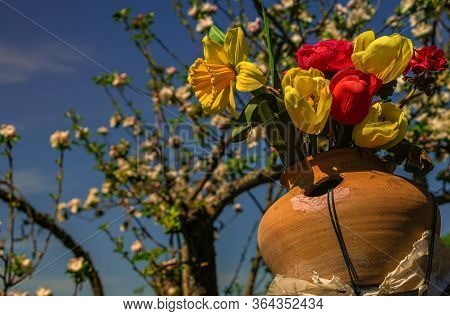 A Bunch Of Artificial And Colorful Flowers In A Handmade Jug