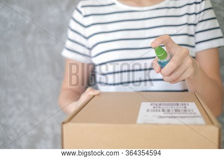 Asian Woman Wears Mask Using Spray Alcohol Sanitizer Cleaning Parcel Post, To Prevent The Virus And