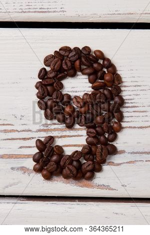 Brown Roasted Coffee Beans Arranged In A Shape Of Nine. Seeds In A Form Of Number Nine On White Wood