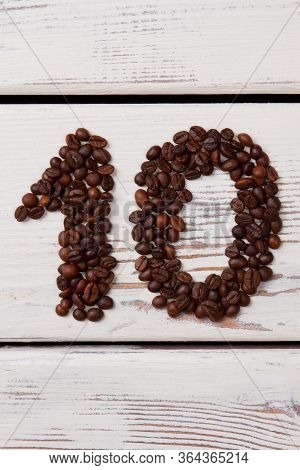 Brown Coffee Beans Arranged In A Shape Of Number Ten. Coffee Seeds On White Wooden Planks Making Hea