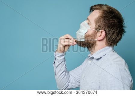 Bearded Man In A Medical Mask, Which Does Not Fit Snugly Due Unshaven Face. Copy Space. Concept Of S