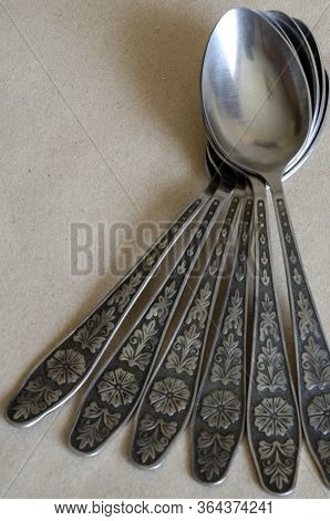 A Few Tablespoons On The Table. Metal Spoons Dry After Washing. Stainless Steel Spoons With Ornament