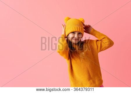 Smilng Little Girl Wearing Nice Yellow Hat And Sweater