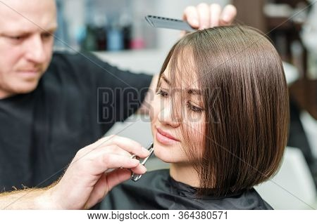 Stylist Is Cutting Woman Hair And Making New Hairdress In Salon. Hairdresser Cutting Clients Hair In