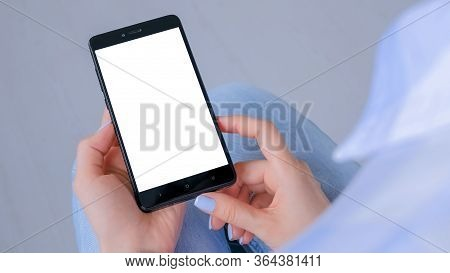 Over Shoulder View: Woman Hands Holding Black Smartphone With White Blank Screen In Home Interior. M