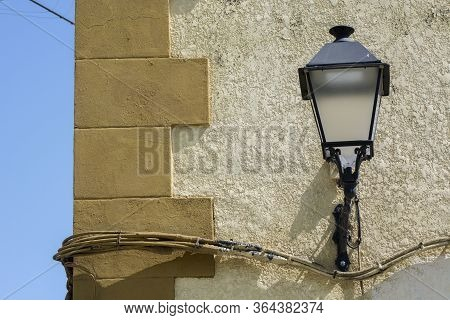 Photo Of A Building Facade Detail With Streetlight, Several Colours And Sunlight.