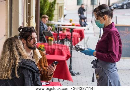 Vilnius, Lithuania - April 30 2020: Waitress With A Mask And Clients Without Mask At An Outdoor Bar,