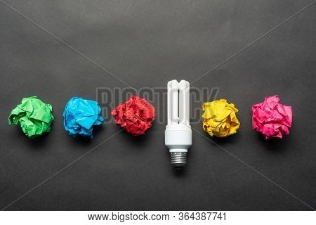 Fluorescent Lamp And Crumpled Colorful Paper Balls On Black Background. Successful Solution Of Probl