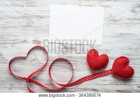 Flat Lay Composition With Red Love Hearts And Ribbon. Blank Sheet Of White Paper On Vintage Wooden T