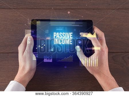 Close-up of hands holding tablet with PASSIVE INCOME inscription, modern business concept