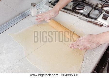 Female Hands Are Holding Rolling Pin Sprinkled With Flour. Chef At Work On Pizza. Сook Rolls Out The