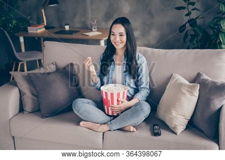 Portrait Of Candid Dreamy Cute Girl Sit Divan Legs Crossed Folded Hold Big Pop Corn Box Watch Intere