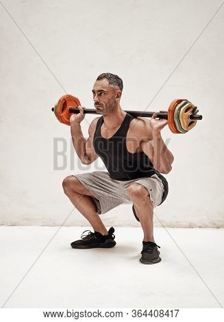 Adult Crossfit Athlete Holding Barbell Overhead While Squatting, Isolated In A Bright Studio And Wea
