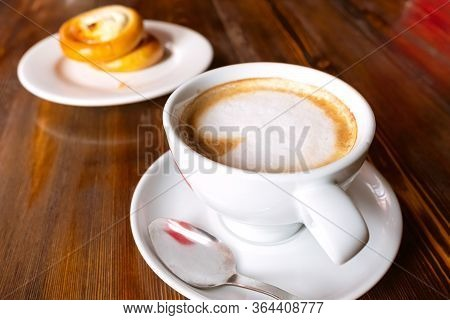 Cup With Cappuccino And Saucer With A Bun. Bun With Cottage Cheese And Cappuccino Coffee On A Wooden