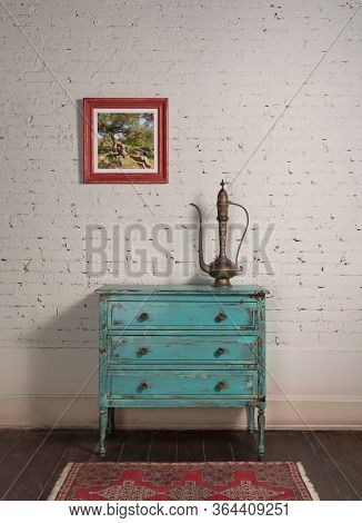 White Brick Wall With Copper Antique Tea Pot On The Top Of Shabby Chic Vintage Turquoise Cabinet And