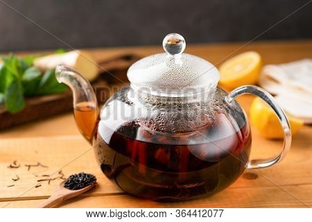 Glass Tea Pot With Black Tea On A Wooden Table. Healthy Drink. Chinese Tea With Ginger, Lemon And Mi