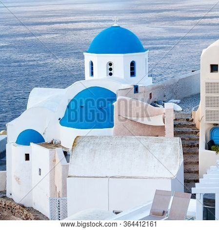 Famous Blue Domed Greek Church In Oia Town And Sea View On Santorini Island, Cyclades, Greece