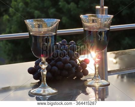 Wine For Two - Glasses Of Red Wine And Some Dark Grapes On A Glass Table On The Park Side, Sunset An