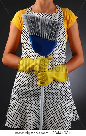 Closeup of a homemaker in an apron holding a broom in front of her torso. Vertical format over a light to dark background. Woman is unrecognizable.