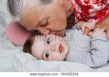 Grandmother Is Kissing Her Baby Granddather Indoors. Senior Woman Kisses Baby Girl. Multi Generation